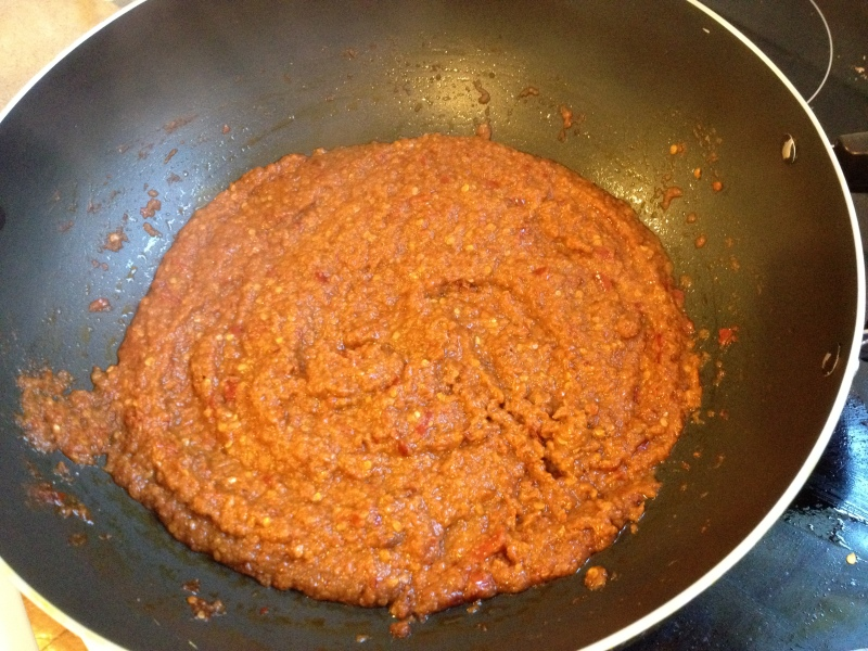 Add paste to a heated wok and fry until oil oozes